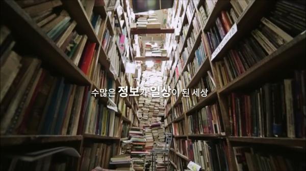 책으로 가득 찬 책장이 양 옆에 서 있고 책장 사이 복도에 책이 천장까지 쌓여있다. 이미지 가운데 글 '수많은 정보가 일상이 된 세상'